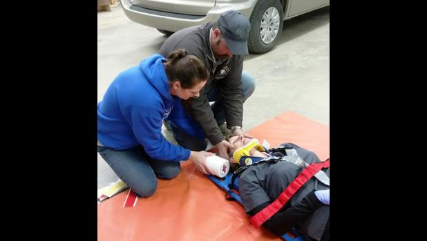Vanessa Hight plays patient to Lacie Campbell and Chris Letellier as they practice spinal immobilization and backboarding skills.