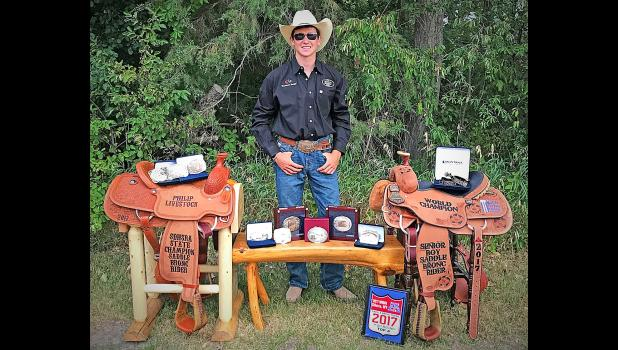 Cash Wilson, a junior at  Wall High School, stands behind his hard work, accomplishments, and earnings from this summer. Pictured are his winnings since the first week of June 2017: two saddles, nine buckles, and a set of spurs.
