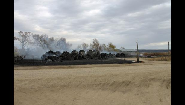 Long stacks of round hay bales across the countryside smolder in the aftermath of the Cottonwood Fire.