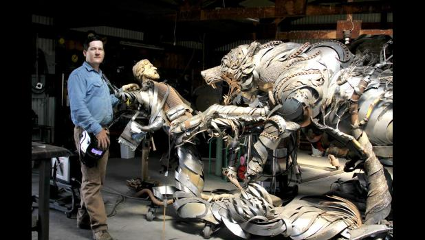 Lopez with the sculpture he is creating out of scrap metal.